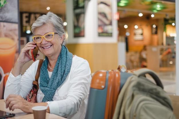 Jolie femme âgée assise au café de l'aéroport parlant au téléphone portable en attendant l'embarquement. le voyageur mûr heureux boit du café