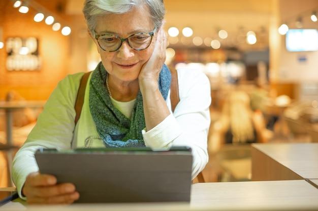 Jolie femme âgée assise au café de l'aéroport en utilisant les médias sociaux sur tablette numérique en attendant l'embarquement. voyageur mûr heureux en vacances