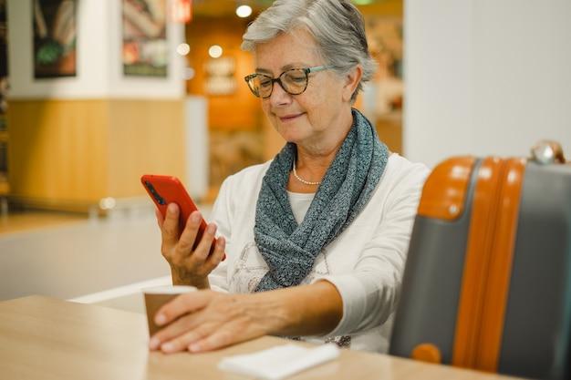 Jolie femme âgée assise au café de l'aéroport utilisant les médias sociaux sur téléphone portable en attendant l'embarquement. voyageur mûr heureux avec des bagages