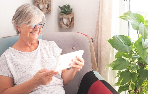 Jolie femme âgée assise sur le fauteuil et regardant la tablette. cheveux gris, lunettes et grand sourire. fond avec plante naturelle et fenêtre. un seul peuple