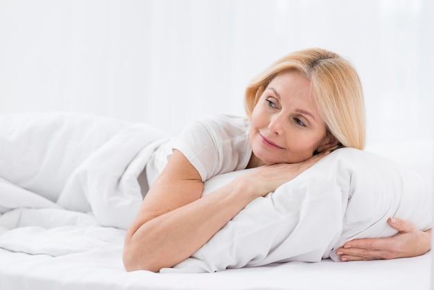 Jolie femme âgée tenant un oreiller