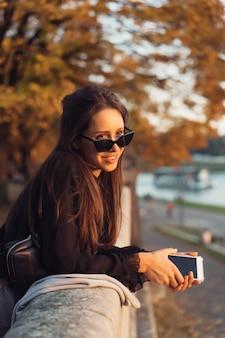Jolie femme à l'aide de smartphone en plein air dans le parc