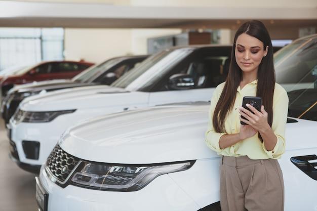 Jolie femme à l'aide de son téléphone intelligent tout en passant voiture neuve