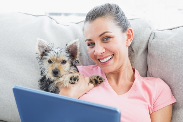 Jolie femme à l'aide de tablet pc avec son yorkshire terrier