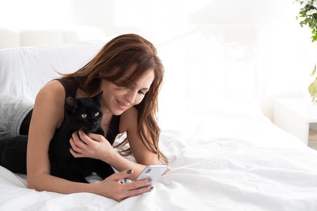 Jolie femme à l'aide de téléphone avec son chat noir, portant ensemble dans la chambre blanche