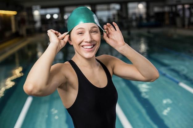 Jolie femme ajustant son bonnet de bain à la piscine