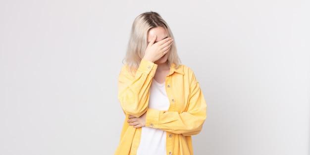 Jolie femme albinos à l'air stressée, honteuse ou contrariée, avec un mal de tête, couvrant le visage avec la main
