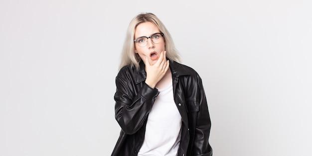 Jolie femme albinos avec la bouche et les yeux grands ouverts et la main sur le menton, se sentant désagréablement choquée, disant quoi ou wow