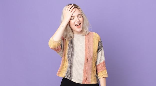 Jolie femme albinos riant et giflant le front comme pour dire dã¢â€â™oh! j'ai oublié ou c'était une erreur stupide