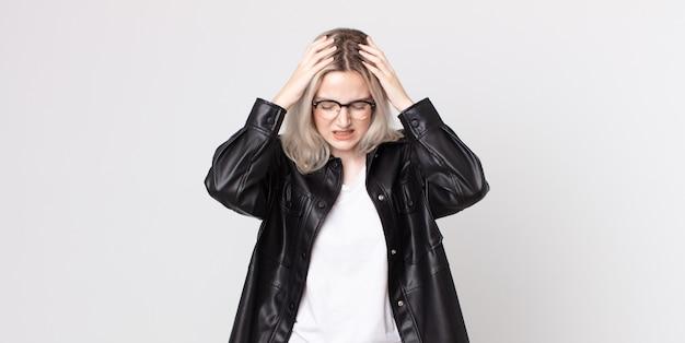 Jolie femme albinos se sentant stressée et frustrée, levant les mains à la tête, se sentant fatiguée, malheureuse et souffrant de migraine