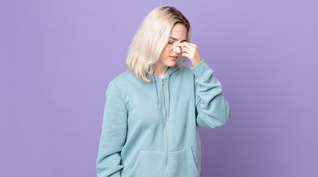 Jolie femme albinos se sentant stressée, malheureuse et frustrée, touchant le front et souffrant de migraine de maux de tête sévères