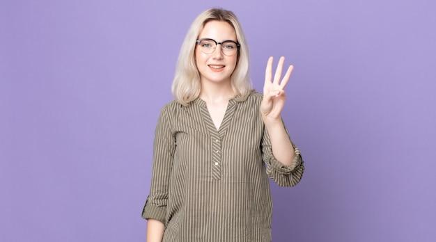 Jolie femme albinos souriante et semblant amicale, montrant le numéro trois ou troisième avec la main en avant, compte à rebours