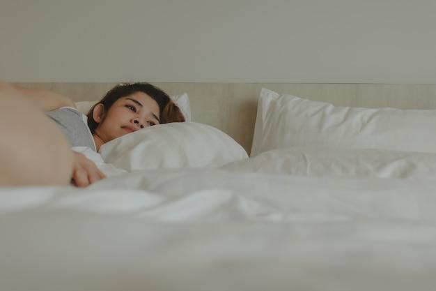Jolie femme allongée sur le lit se sentant détendue et confortable le matin