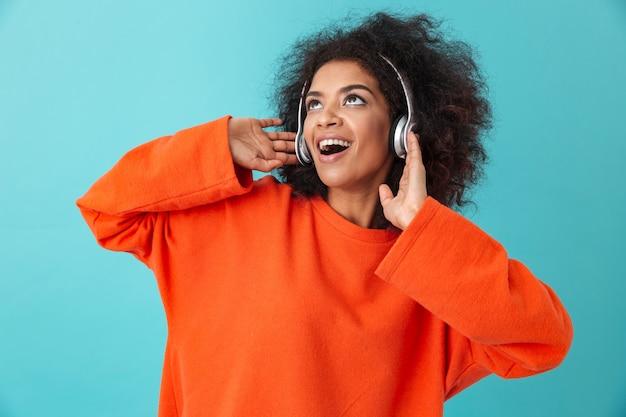 Jolie femme américaine en chemise orange appréciant la musique via des écouteurs sans fil tout en écoutant la mélodie préférée, isolée sur le mur bleu