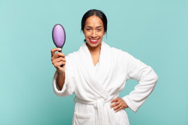 Une jolie femme américaine. expression heureuse et surprise.. concept de brosse à cheveux concept de brosse à cheveux