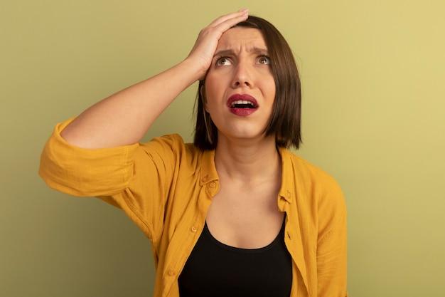 Jolie femme anxieuse met la main sur le front et lève les yeux isolé sur mur vert olive