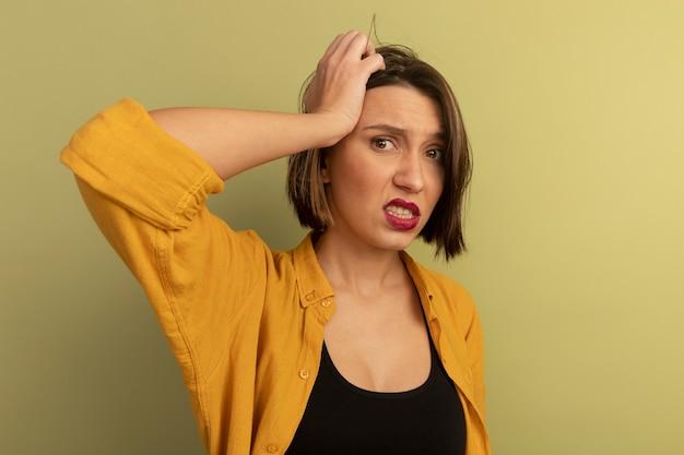 Jolie femme anxieuse met la main sur la tête isolée sur un mur vert olive