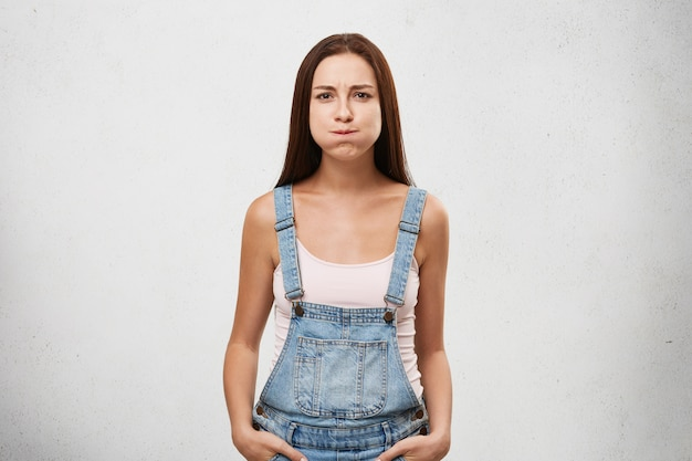 Jolie femme d'apparence européenne vêtue d'une combinaison en denim retenant son souffle, s'efforçant de ne pas rire.