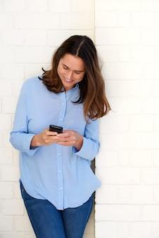 Jolie femme appuyée contre le mur et regardant le téléphone portable