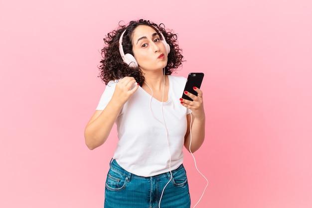 Jolie femme arabe à l'air arrogante, réussie, positive et fière avec des écouteurs et un smartphone