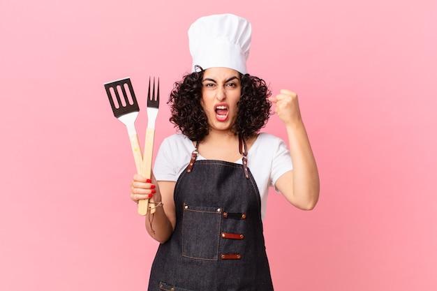 Jolie femme arabe criant agressivement avec une expression de colère. concept de chef de barbecue