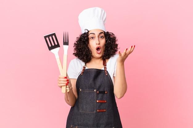 Jolie femme arabe émerveillée, choquée et étonnée d'une incroyable surprise. concept de chef de barbecue
