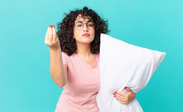Jolie femme arabe faisant un geste de capice ou d'argent, vous disant de payer. porter un pyjama et tenir un oreiller