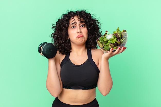 Jolie femme arabe avec un haltère et une salade. concept de remise en forme