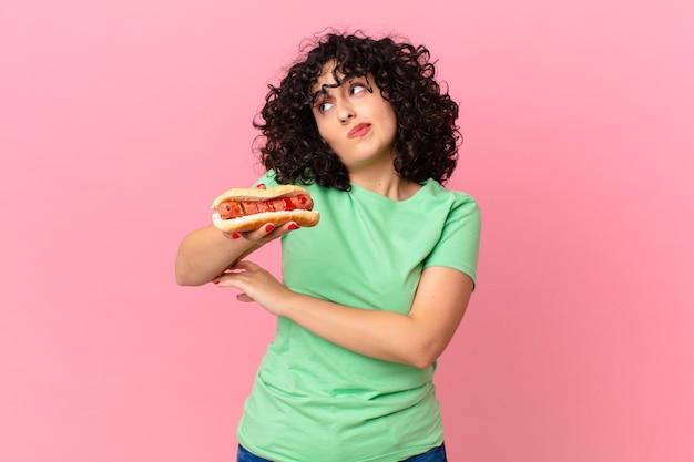 Jolie femme arabe haussant les épaules, se sentant confuse et incertaine et tenant un hot-dog