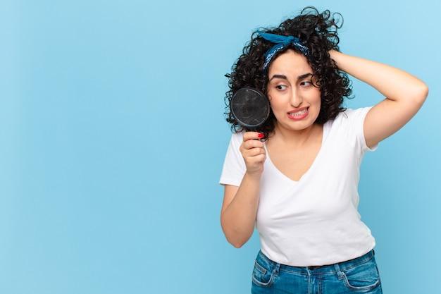 Jolie femme arabe avec une loupe