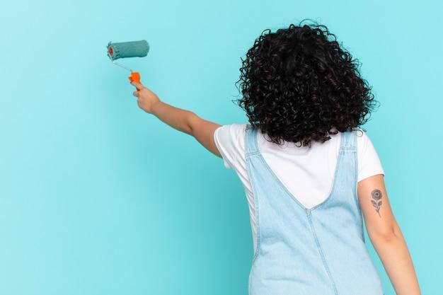 Jolie femme arabe peignant le concept de mur de maison