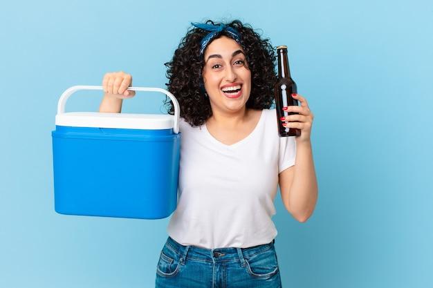 Jolie femme arabe avec un réfrigérateur portable et une bière