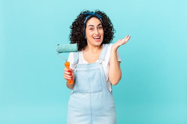 Jolie femme arabe se sentant heureuse et étonnée de quelque chose d'incroyable. concept de maison de peinture