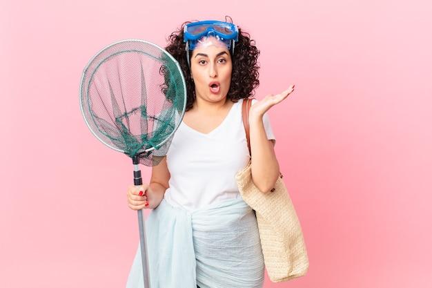 Jolie femme arabe semblant surprise et choquée, avec la mâchoire tombée tenant un objet avec des lunettes. concept de pêcheur