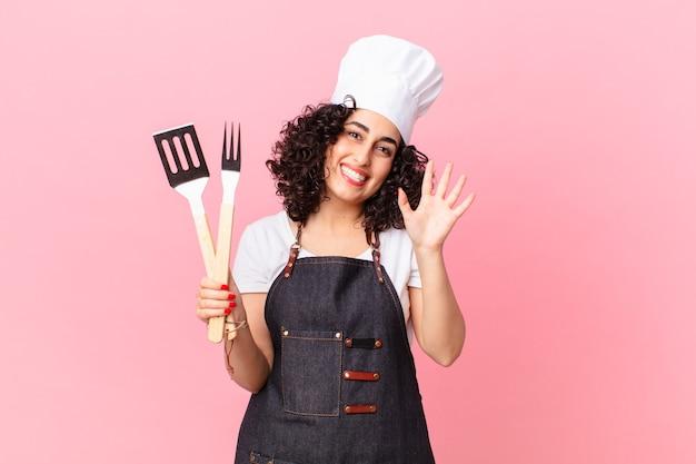 Jolie femme arabe souriant joyeusement, agitant la main, vous accueillant et vous saluant. concept de chef de barbecue