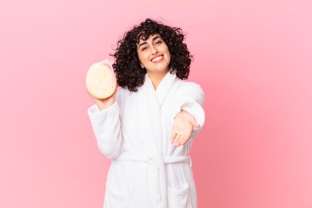 Jolie femme arabe souriant joyeusement avec amicale et offrant et montrant un concept portant un peignoir et tenant une éponge