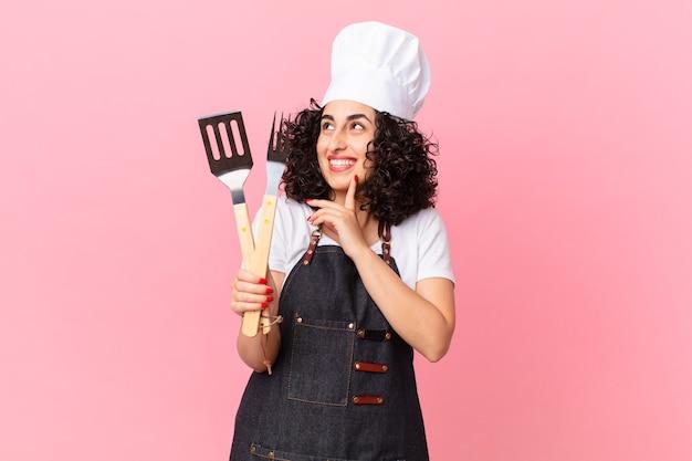 Jolie femme arabe souriant joyeusement et rêvant ou doutant. concept de chef de barbecue
