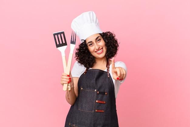 Jolie femme arabe souriante fièrement et en toute confiance faisant numéro un. concept de chef de barbecue