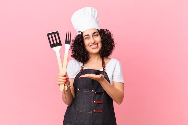 Jolie femme arabe souriante joyeusement, se sentant heureuse et montrant un concept. concept de chef de barbecue