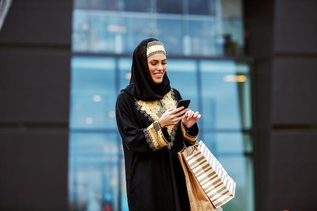 Jolie femme arabe en vêtements traditionnels debout devant le centre commercial avec des sacs à provisions dans les mains et à l'aide d'un téléphone intelligent pour lire ou envoyer un message.