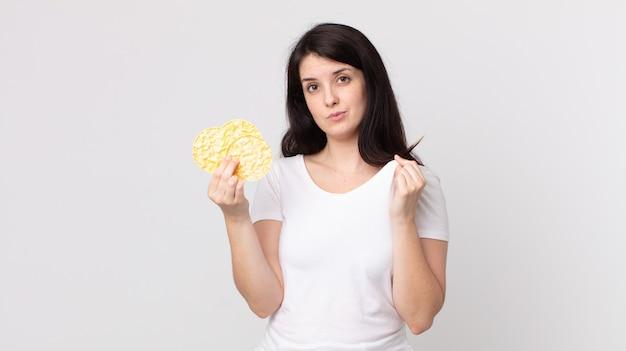 Jolie femme arrogante à la réussite positive et fière et tenant un régime de gâteaux de riz