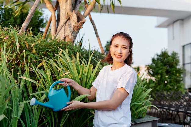 La jolie femme arrosant des fleurs, des plantes dans son jardin.
