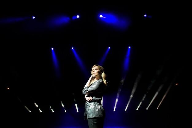 Jolie femme artiste sur fond de projecteurs flous sur la scène