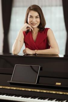 Jolie femme asiatique d'âge moyen en robe rouge debout et à la recherche d'appareil photo avec confiance en soi devant un piano et une tablette. idée pour les femmes apprenant une nouvelle compétence de cours de musique en ligne à la maison.
