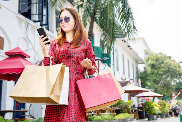 Jolie femme asiatique à l'aide de téléphone portable tout en maintenant les sacs shopping