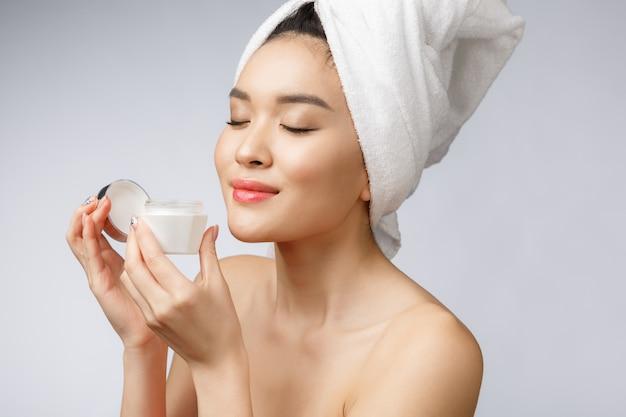Jolie femme asiatique, application de crème sur sa peau, isolée sur blanc.