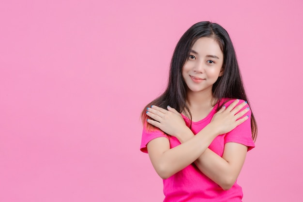 Jolie femme asiatique blanche pose et aime elle-même sur une rose.