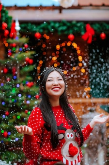 Jolie femme asiatique brune en pull de noël rouge et arc rouge posant