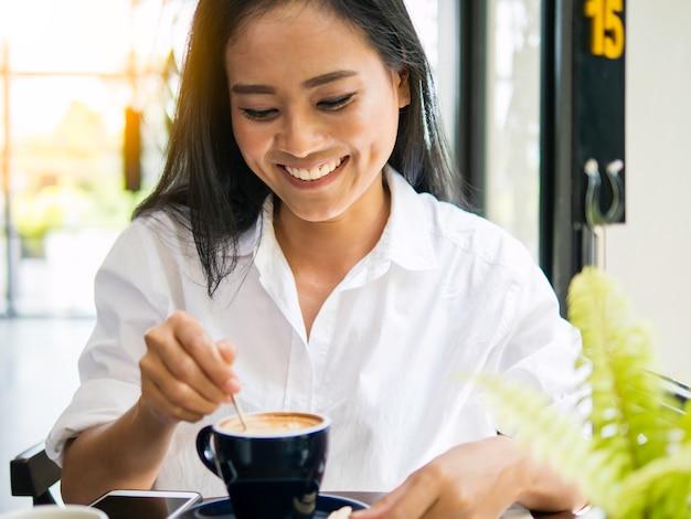 Jolie femme asiatique buvant du café chaud, détendue, heureuse