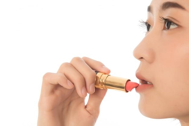 Jolie femme asiatique cheveux courts appliquant le rouge à lèvres isolé sur blanc